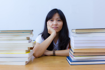 Bored  asian college student in uniform with stack of books