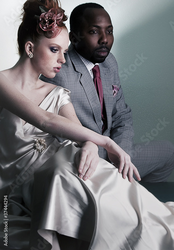 Two fashion models sitting - black man and red head woman