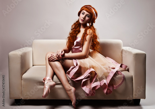 The image of a beautiful woman in luxurious dress sitting on sof