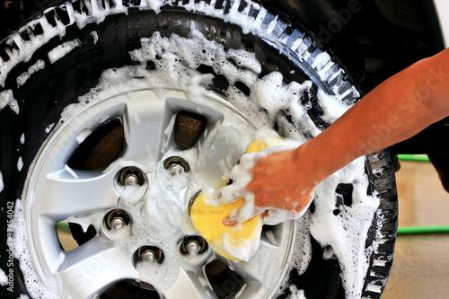 Washing a car tire. With a sponge and shampoo