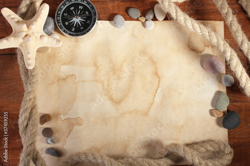 old paper, compass and rope on a wooden table