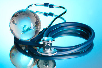 Globe and stethoscope on blue.