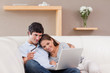 Happy couple booking holiday online