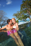 Cheerful couple swimming in resort pool