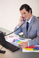 Smiling businessman talking about statistics on the phone