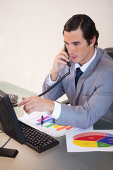 Businessman talking on the phone while working on statistics