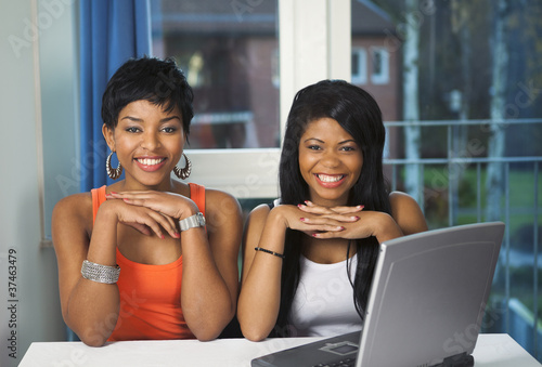 Happy girls viewing online service on laptop