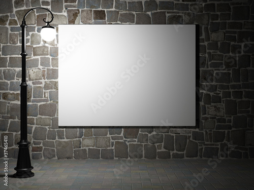 Blank billboard on a brick wall at night.