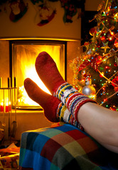 girl resting in a room with a burning fireplace and Christmas tr