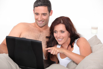 A nice couple in bed with a laptop.
