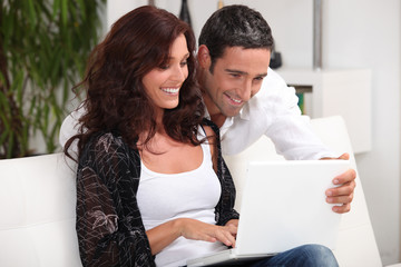 Couple looking at photos on their laptop and reminiscing