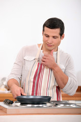 Young man in apron cooking