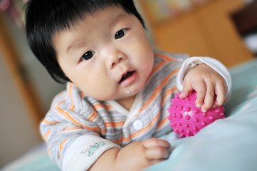 An Asian baby lying on the bed
