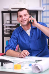 blue collar worker in his office and on the phone