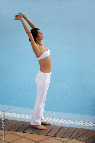 Healthy woman stretching at a poolside