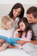 Portrait of a family reading a book
