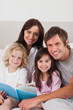 Portrait of a happy family reading a book