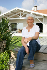 Elderly lady sat on decking