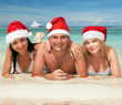 Happy friends in santa hats on the beach
