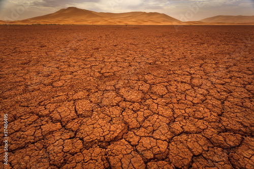 Fotobehang Woestijn Cracked pattern of dry lake bed and sand dunes in Sahara Desert