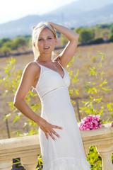 Hübsche blonde Frau im weißen Kleid