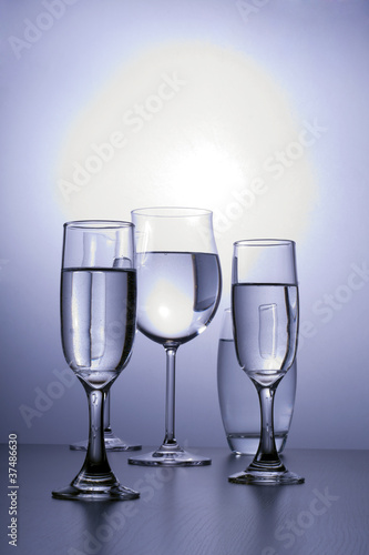 Alcoholic glasses line next to each other.