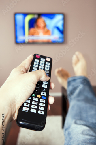 Young man watching the television, the remote control in hand.