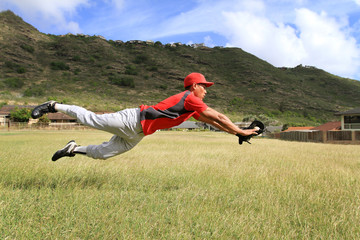 Baseball player dives to catch the ball