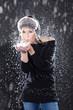 Hübsche junge Frau pustet Schnee