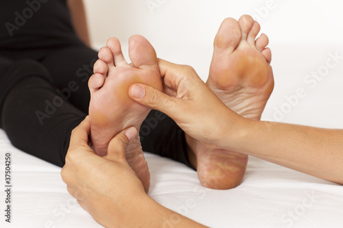 hands massaging a woman's foot