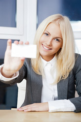 Young businesswoman showing her business card - sitting at her o