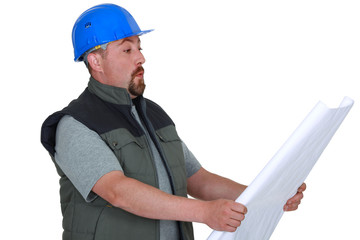 Surprised tradesman looking at a blueprint