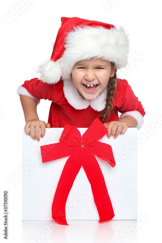 Happy little girl in Santa hat looks out of gift box