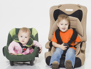 Two kid sit in automobile armchairs