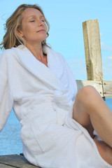 Woman relaxing in the sunshine in a towelling robe