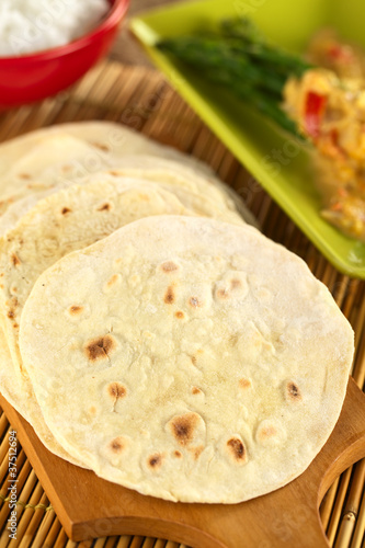 Indian flatbread called chapati on wooden board