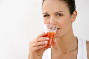 Woman drinking glass of carrot juice