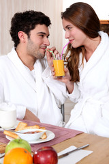 young couple in bathrobe drinking orange juice out of straw
