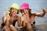 Two female friends at the beach giving thumbs-up