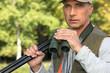 Hunter with a shotgun and pair of binoculars