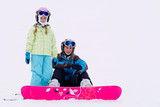 Snowboarding, skiing - portrait of young girls on ski slope