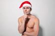 Man shirtless wearing Santa hat with finger on lips