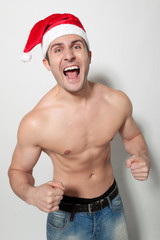 Man shirtless wearing Santa hat celebrating success shouting
