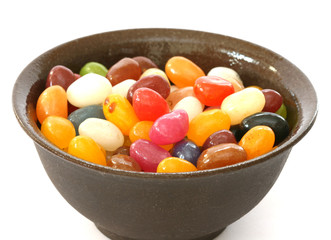 Colourful candies in a bowl on white background