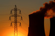 high voltage tower and power plant during sunset