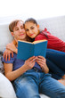 Romantic couple sitting on sofa and reading book