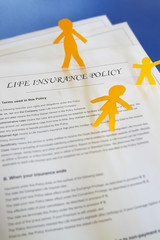 life insurance policy and paper cutout family