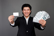 asian man holding money and card