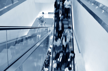 business people on the escalator