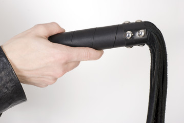 Black Leather Flogging Whip in female hand.